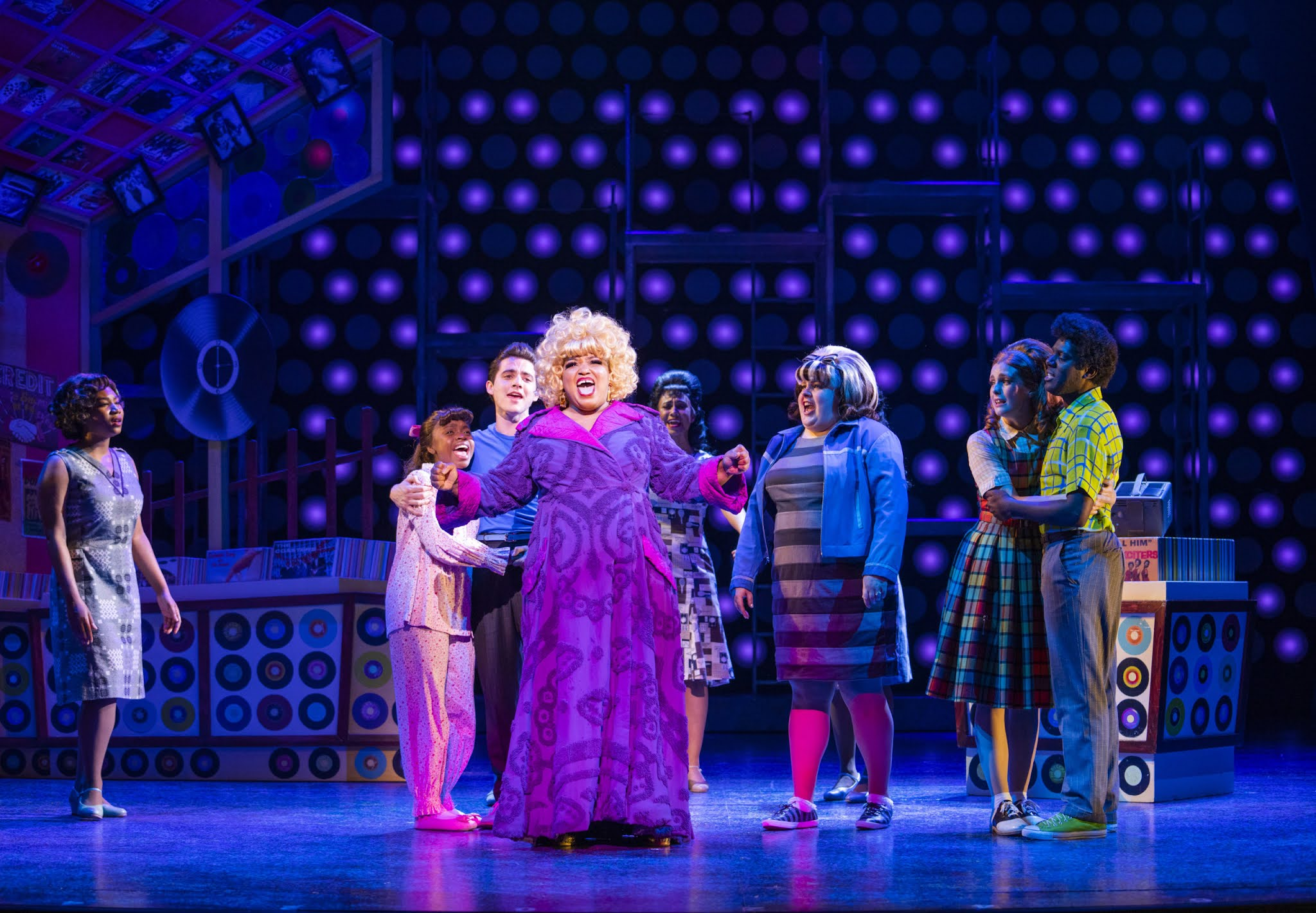 Marisha Wallace is performing on stage at Hairspray the musical in the west end as Motormouth Mabel, she is wearing a long purple coat with a 60s print on it and a blonde curly wig.
