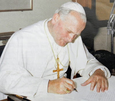 Saint John Paul II writing at his desk.
