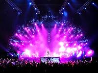 Büyük bir konser alanındaki yarım küre şeklindeki ışıklı sahne içinde sanatçı şarkı söylerken