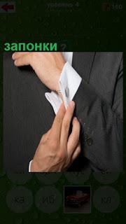 мужчина застегивает запонки на рукаве рубашки