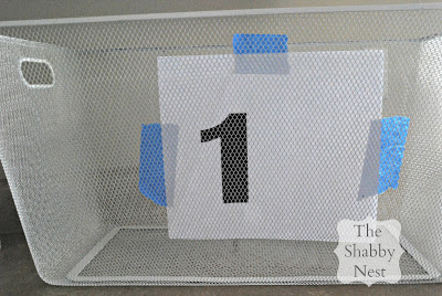 Use painters' tape to affix number to inside of basket