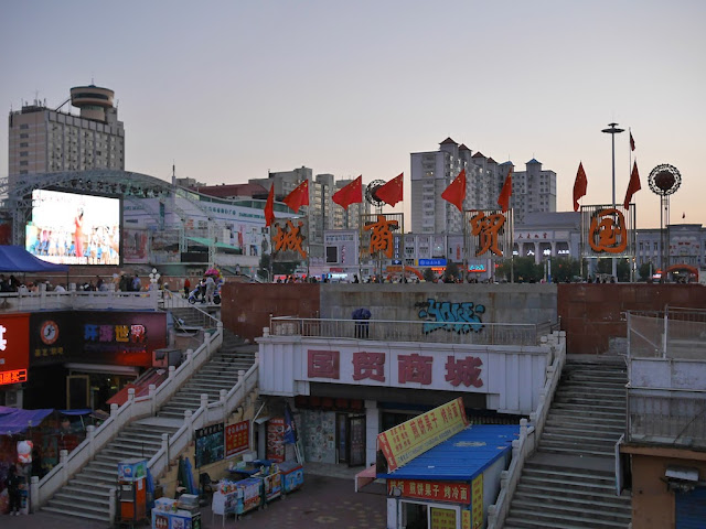 Chinese flags on the main sign for the Guomao Shopping Center (国贸商城) at Culture Square (文化广场) in Mudanjiang, China