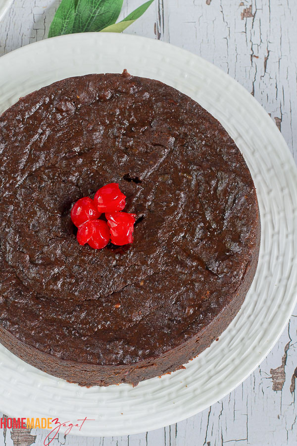 A whole black cake with red cherries on top resting on a white plate
