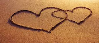 Entwined hearts in sand