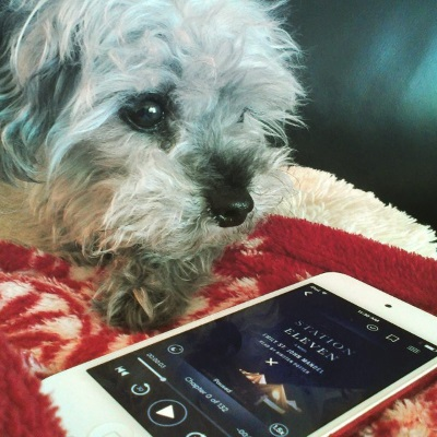 Murchie lies on a fuzzy red and white blanket with his face close to the camera. In front of him is a white iPod with Station Eleven's cover on its screen. The cover features a group of white canvas tents brightly lit from within. A dark blue sky studded with stars stretches above them.