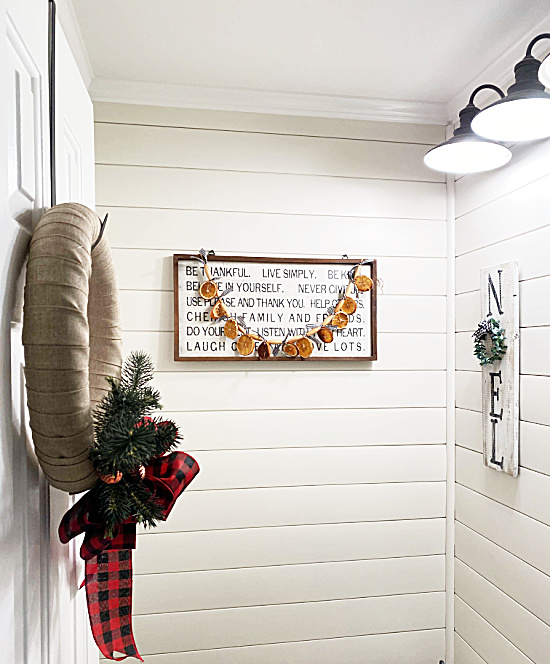 Bathroom with orange slice garland hanging on sign