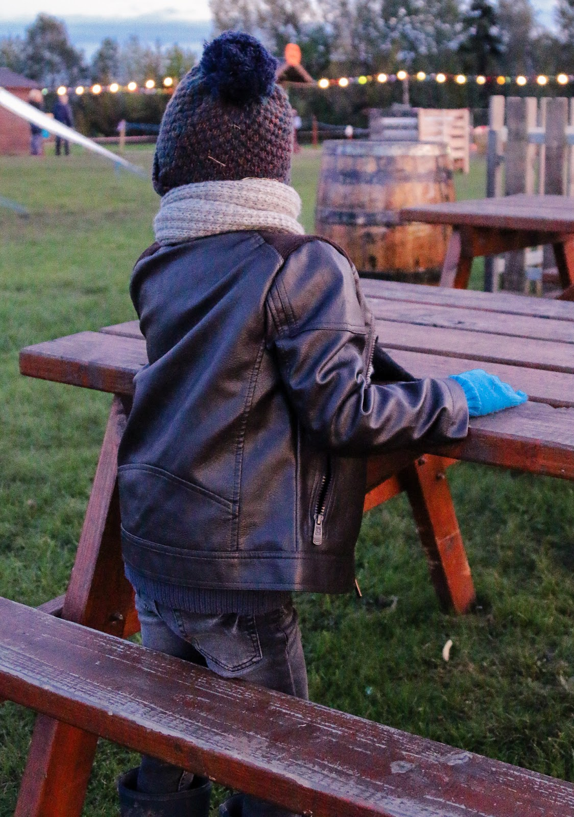 A photo from behind of Little bear sitting on a brown picnic table at M&D's Pumpkin festival