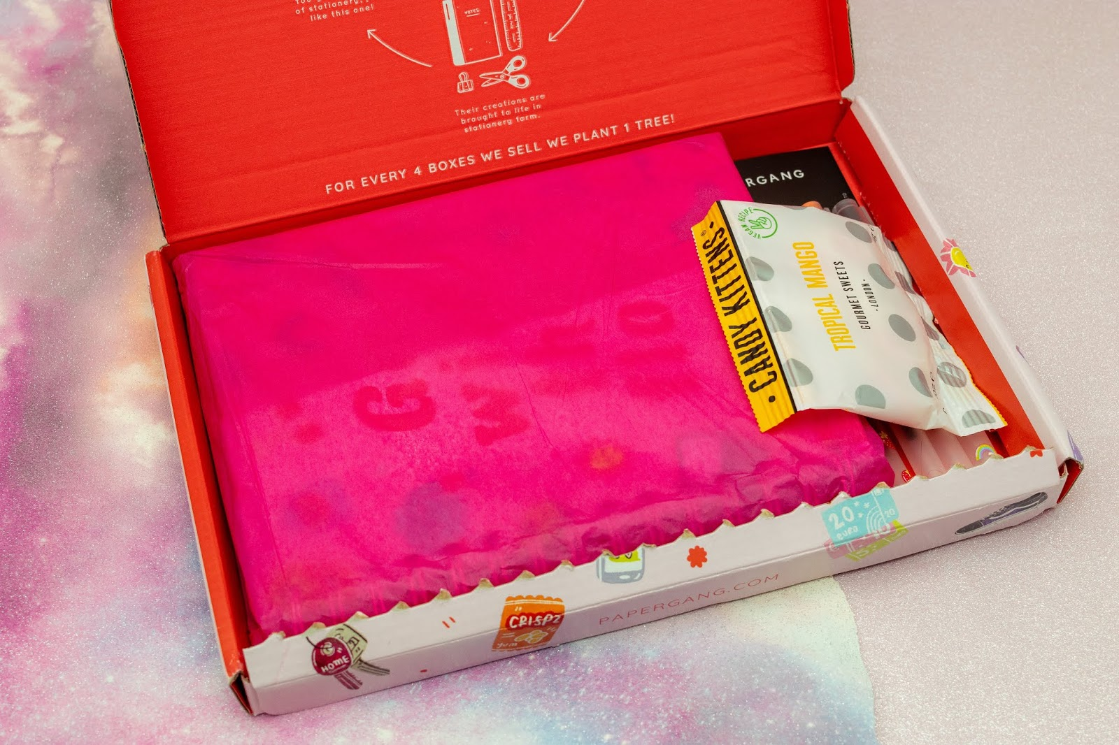 A letterbox sized pink box opened up with hot pink tissue paper and a packet of sweets on the side.