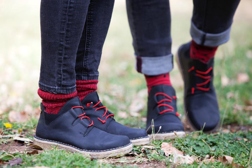 Dos personas usando calzado Tada negro con cordones rojos