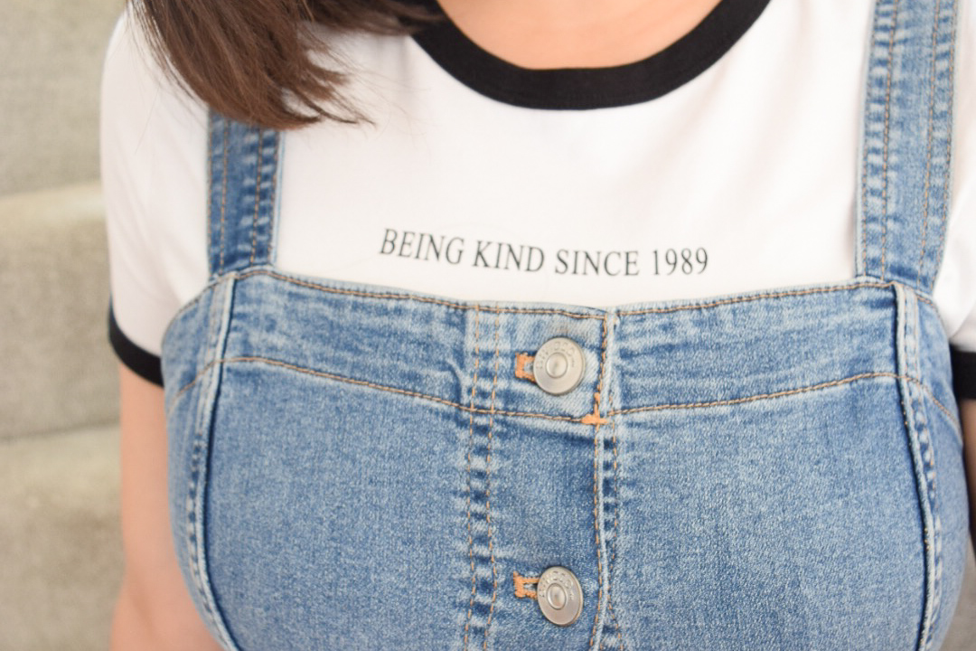 A close up of my outfit. I am wearing a blue button down denim dress with a white t-shirt with black edging. The t-shirt has a slogan that says 'being kind since 1989'.