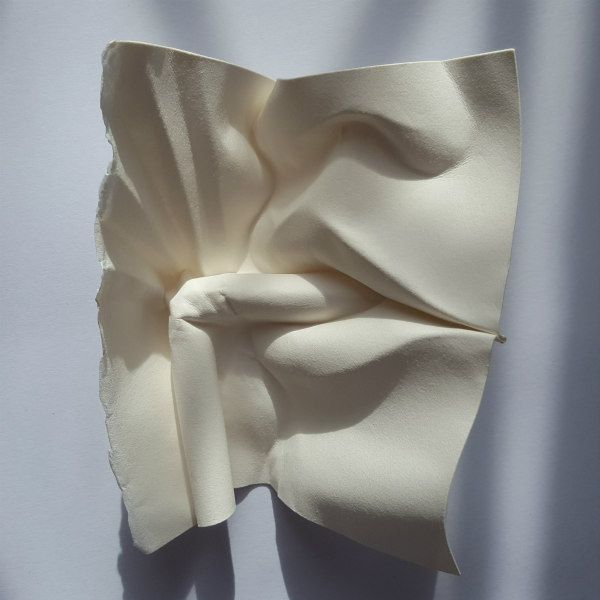 paper sculpture of face holding a bent straw between the lips