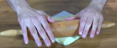 Estirando la mantequilla dentro de un plástico duro para luego dejar reposar en la nevera y formar un cuadrado firme para el hojaldrado