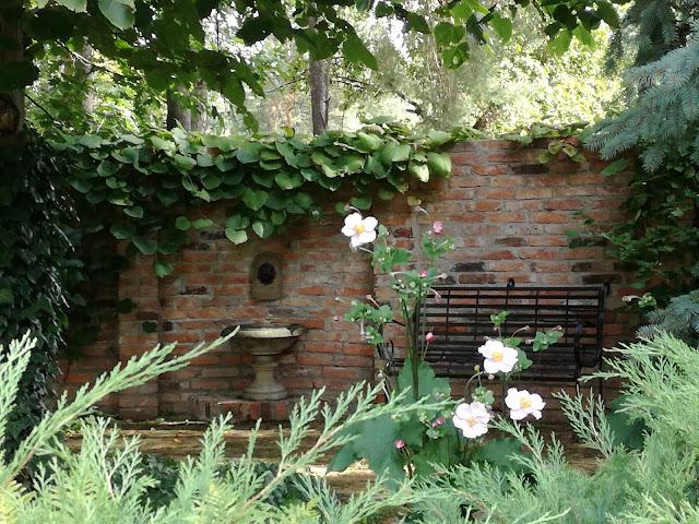 mur z cegły rozbiórkowej w ogrodzie, metalowa ławka ogrodowa