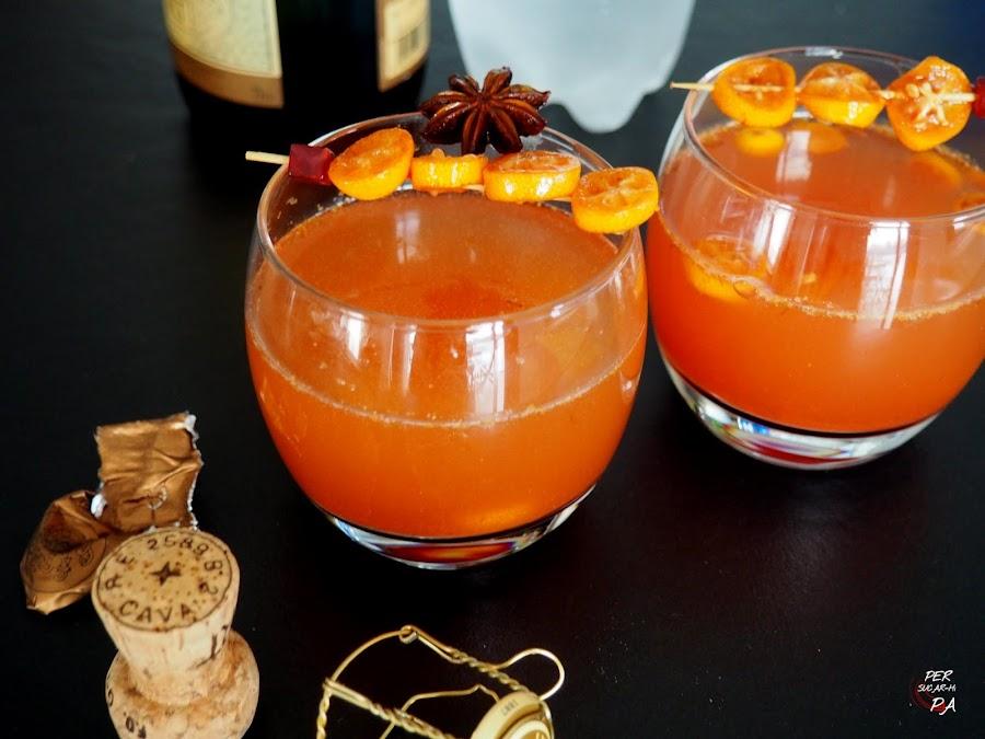 Cóctel rojo de cava para fiestas invernales, a base de sirope de granada, cítricos (kumquats y lima) y especias.
