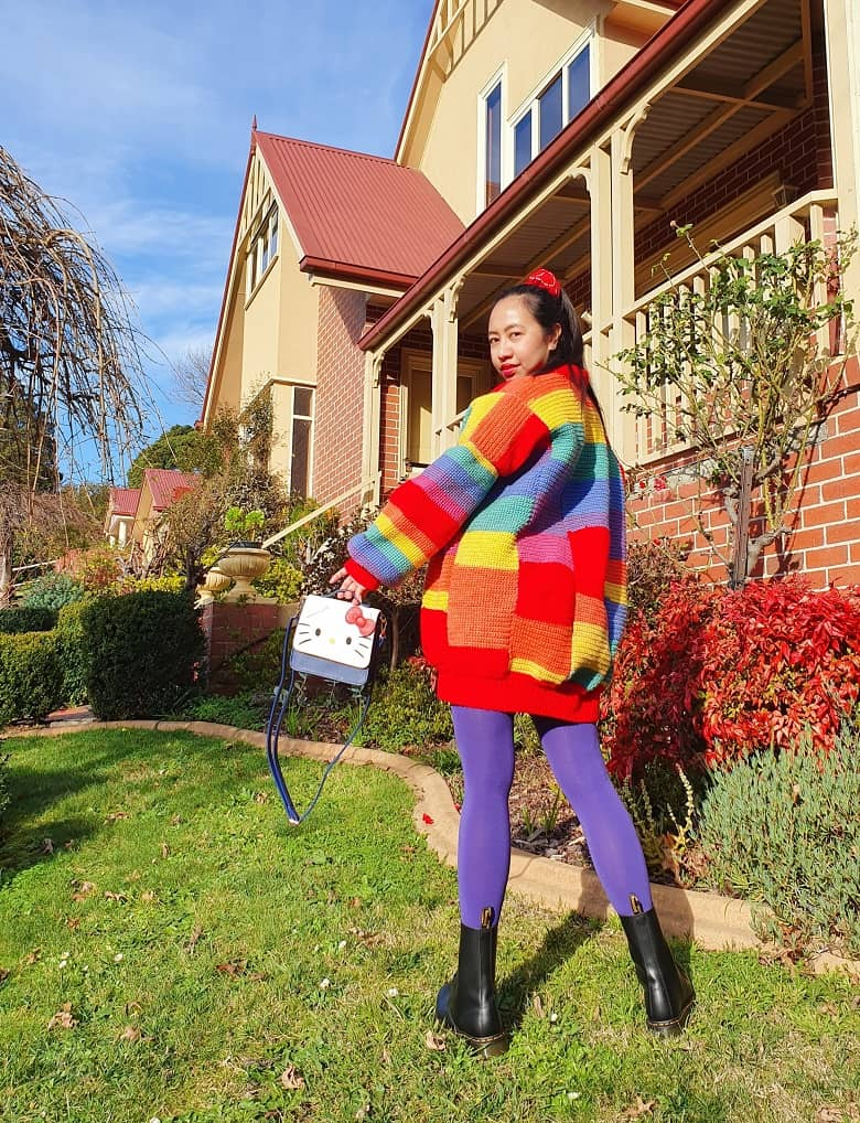 a picture of a girl wearing a crocheted rainbow jumper outdoor
