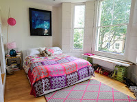 White bright bedroom with bohemian style duvet gray diamond rug with pink trim and lovely lampshades