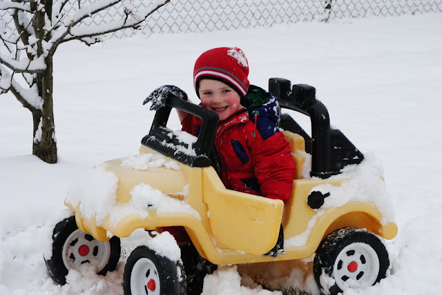 A child playing in a car in the snow