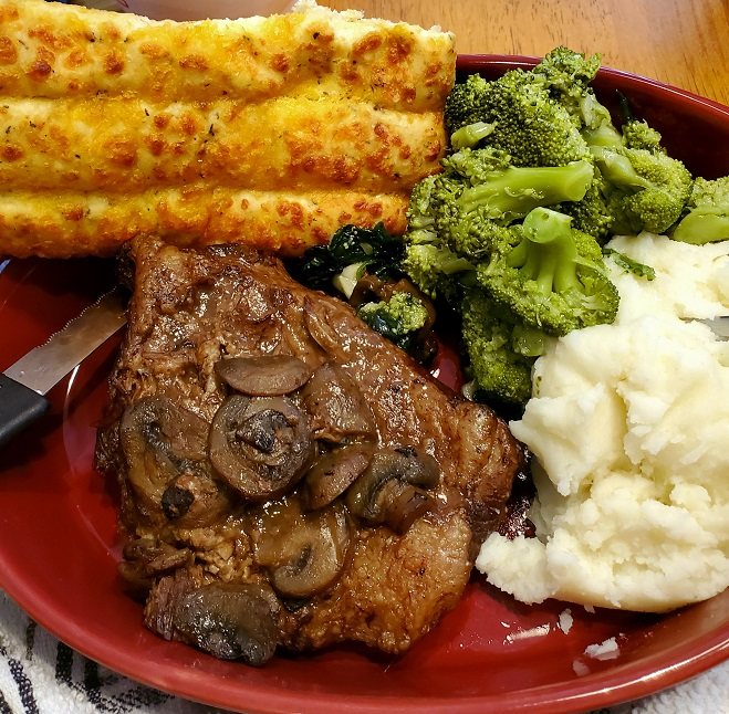 this is steak marsala broccoli, mashed potato garlic bread and spinach
