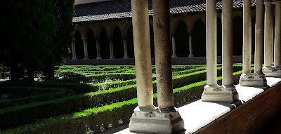 This is an image of tall columns forming a walkway around a square garden