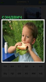 За столом на улице сидит мальчик и ест сэндвич с зеленью