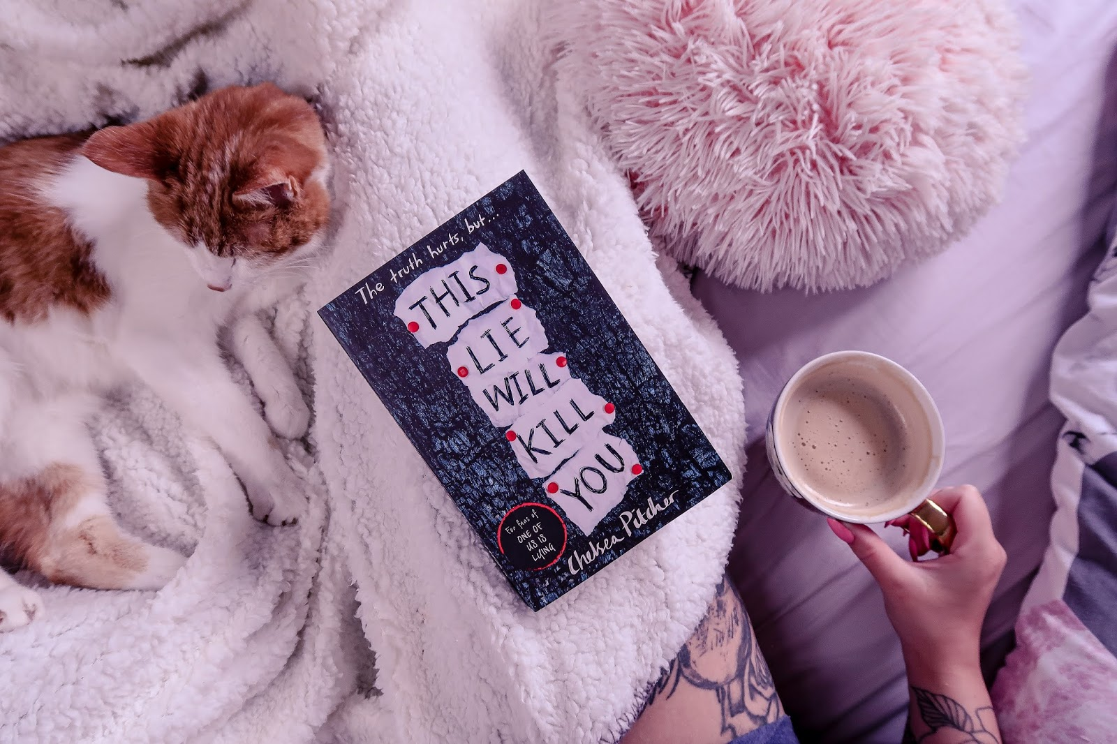 Birds eye view of the book This Lie Will Kill You by Chelsea Pitcher on a white blanket and a cat in the background and pink pillow out of focus with ofaglasgowgirl holding a mug