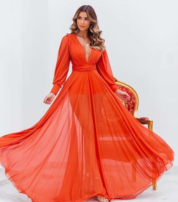vestido longo laranja com mangas longas e transparência na saia