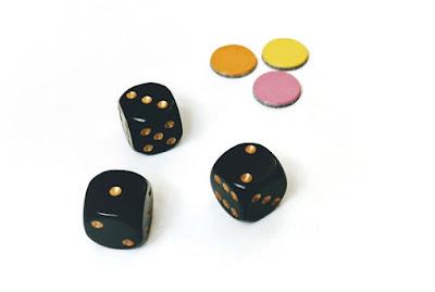 na zdjęciu trzy czarne kostki oraz trzy żetony w różnych kolorach