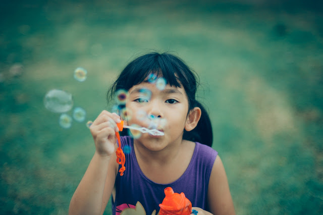 Young girl blowing bubbles towards you