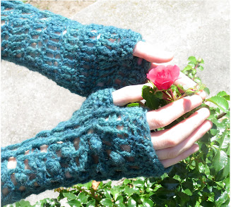 A person wearing a pair of fingerless crochet mittens.  They have their hands around a small flower.