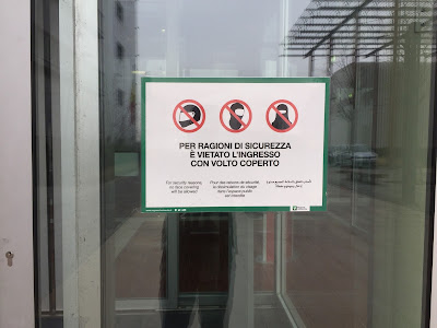 Sign warning you about entering the hospital with a covered face.