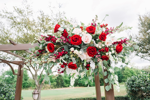 red and pink wedding flowers on ceremony arch