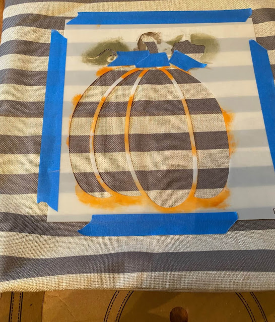 Photo of a pumpkin stencil taped to a pillow cover.