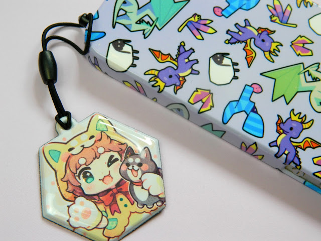 A photo of a charm featuring a girl dressed as a shiba inu dog