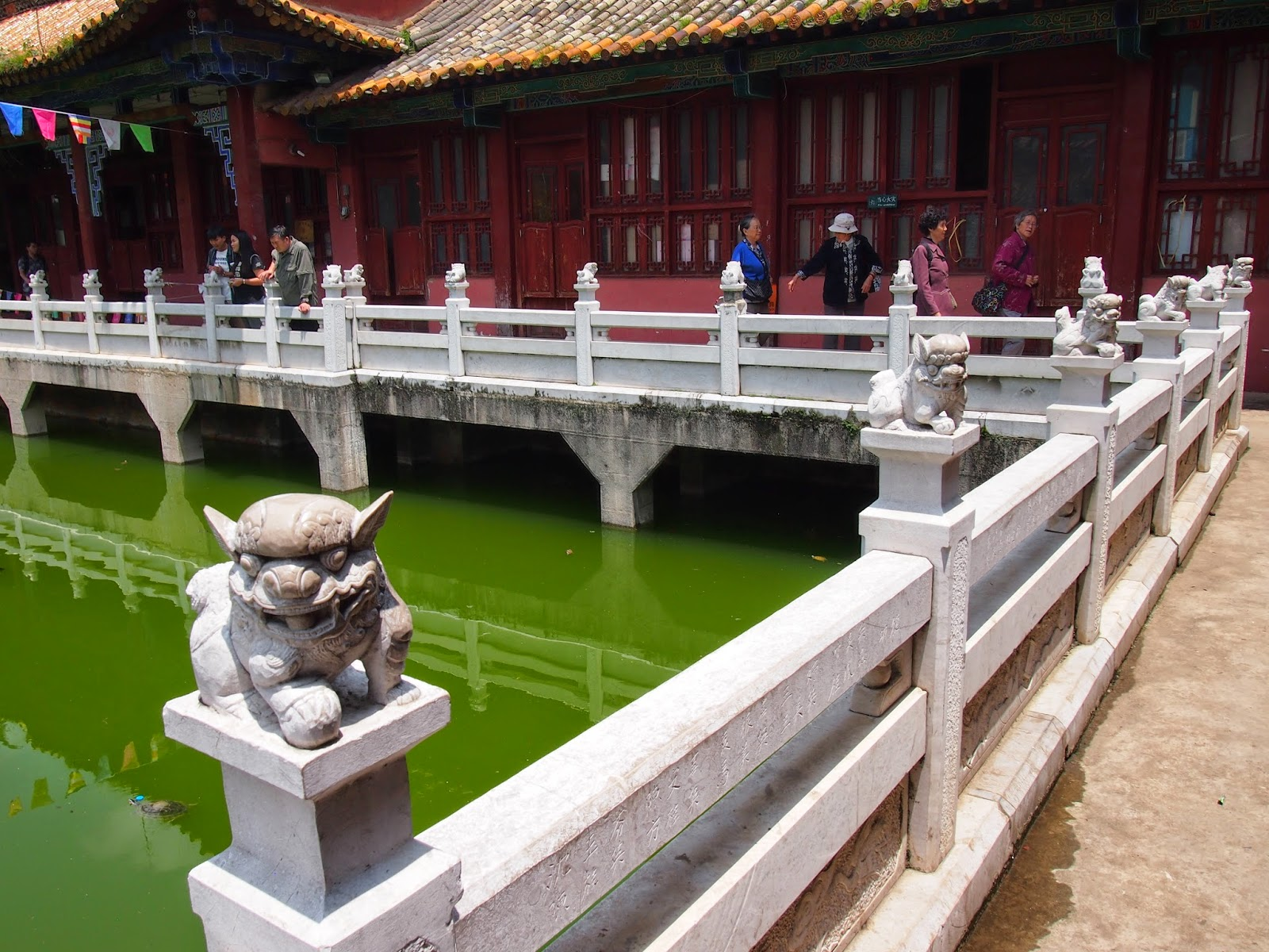 The bright green water and lion statues at the Yuan Tong Temple