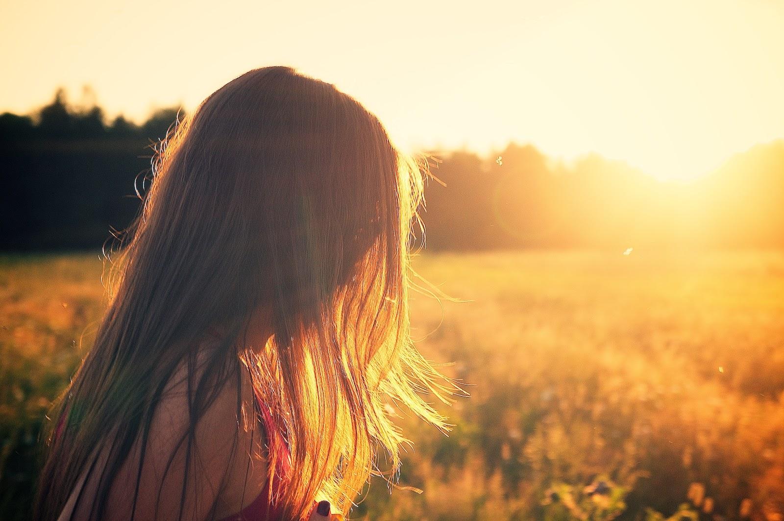 夏の日没の光の中の女性