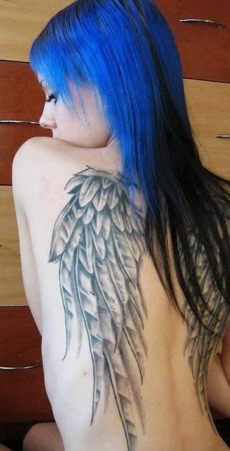 Vemos a una espectacular mujer de cabello azul con tatuajes de aalas