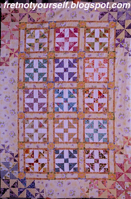 Pastel fabrics in yellow, blue, green and pink are used to make this Grandmother's Dream quilt.