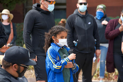 Young girl and community demonstrators in face masks