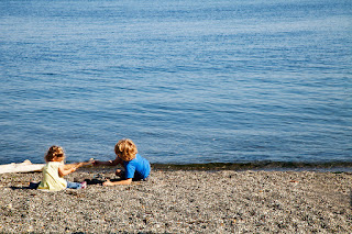 Two children playing on the beach in the town of Port Townsend, Washington