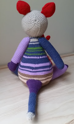 The large crocheted kangaroo is facing away from the camera. One can see the red ears, the back of her beige head, her mauve left arm with a purple paw, blue right arm and multicoloured tail (purple, blue and beige) against the stripes on her body. Her upper body has blue and green stripes, the lower body has beige and brown stripes. Stripe patterns are separated with mauve.