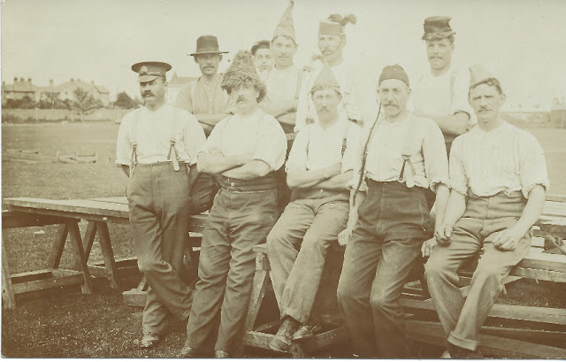 Men resting on wooden tables wearing novelty hats