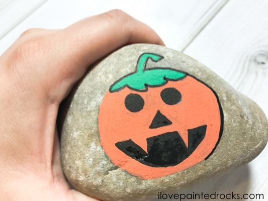 drawing around the halloween pumpkin with a black posca pen