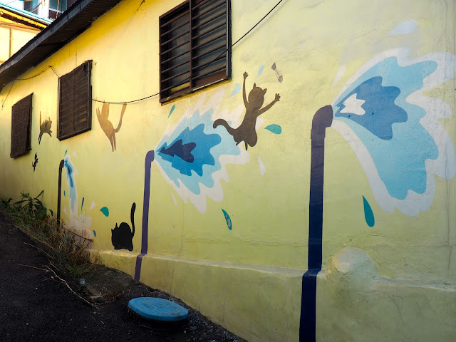 Street art of cats being splashed by water in the Ji-dong mural village in Suwon, South Korea