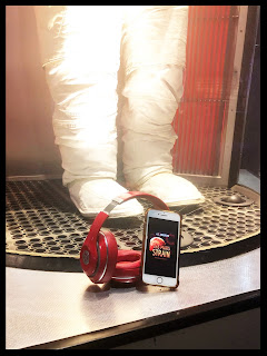 A white NASA astronaut suit behind glass with a pair of red Beats headphones and an iPhone playing audiobook The Mars Strain sitting on the ledge beside it.