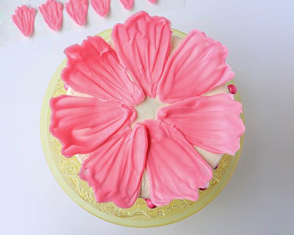 Τοποθετήστε τα μεγαλύτερα πέταλα σε σχήμα κύκλου πάνω στην τούρτα.