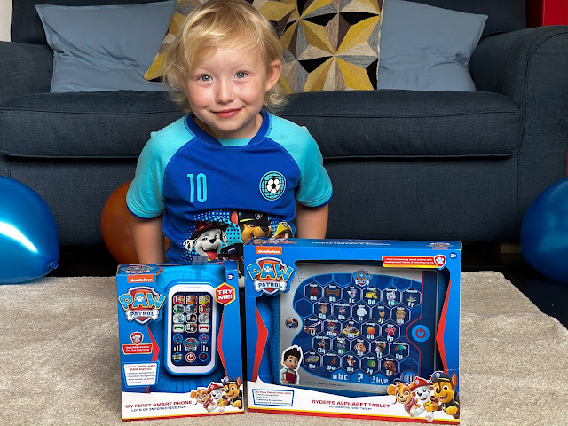 A child in PAW Patrol top sitting behind the PAW Patrol Smart Phone and Alphabet Tablet in their packaging before reviewing them
