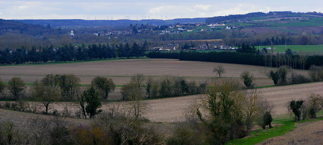 A valley and village view, wind turbines in the distance.  Indre et Loire, France. Photographed by Susan Walter. Tour the Loire Valley with a classic car and a private guide.