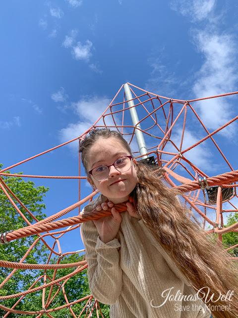 Jolina (Down-Syndrom) auf einem Klettergerüst am Weltspieltag für Stück zum Glück