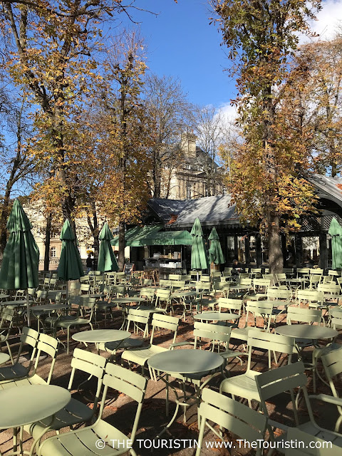 Beergarden with rows of light green chairs and tables under trees in autumn foliage.