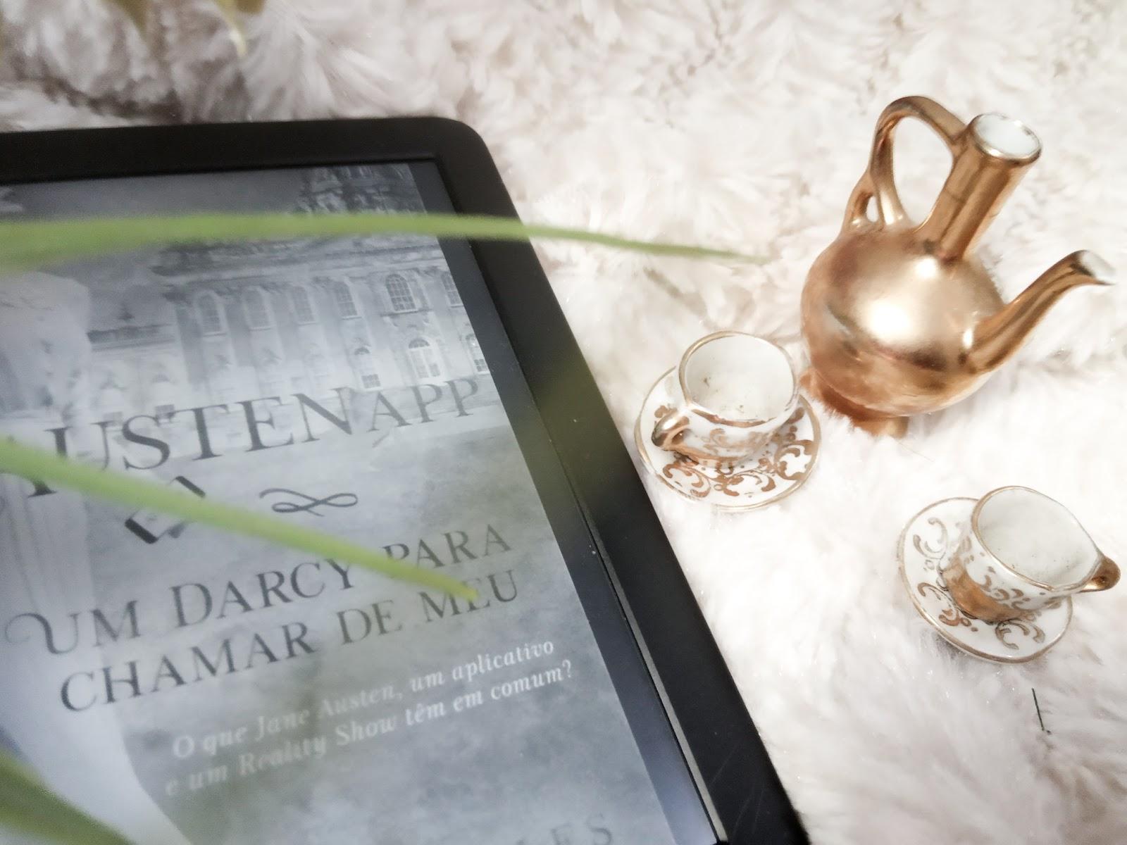Foto com aparelho kindle focado na capa de AustenApp em que aparece os dizeres Um darcy para chamar de meu, ao lado direito ha miniaturas de xicaras, pires e um bule de chá sob um tecido branco e peludo